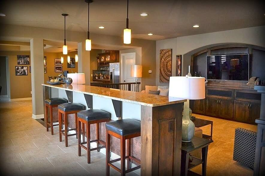 Basement Man Cave With Large Bar Counter Behind The TV Viewing Area