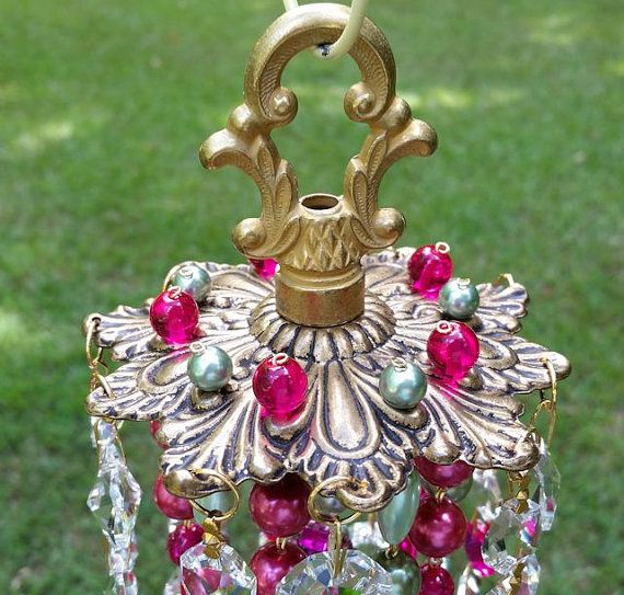 Such a fun and colorful wind chime! Antique scalloped brass top is embellished with green pearls and hot pink glass beads, and the piece is surrounded with layers of crystal prism and bead strands...all in hot pink and various shades of green (from celery to mint). There are hot pink prisms, iridescent green prisms, and peridot green prisms mixed in the strands. This really pops! Attached to the strands are large hot pink french pendant crystals, bright green french pendant crystals, bright…