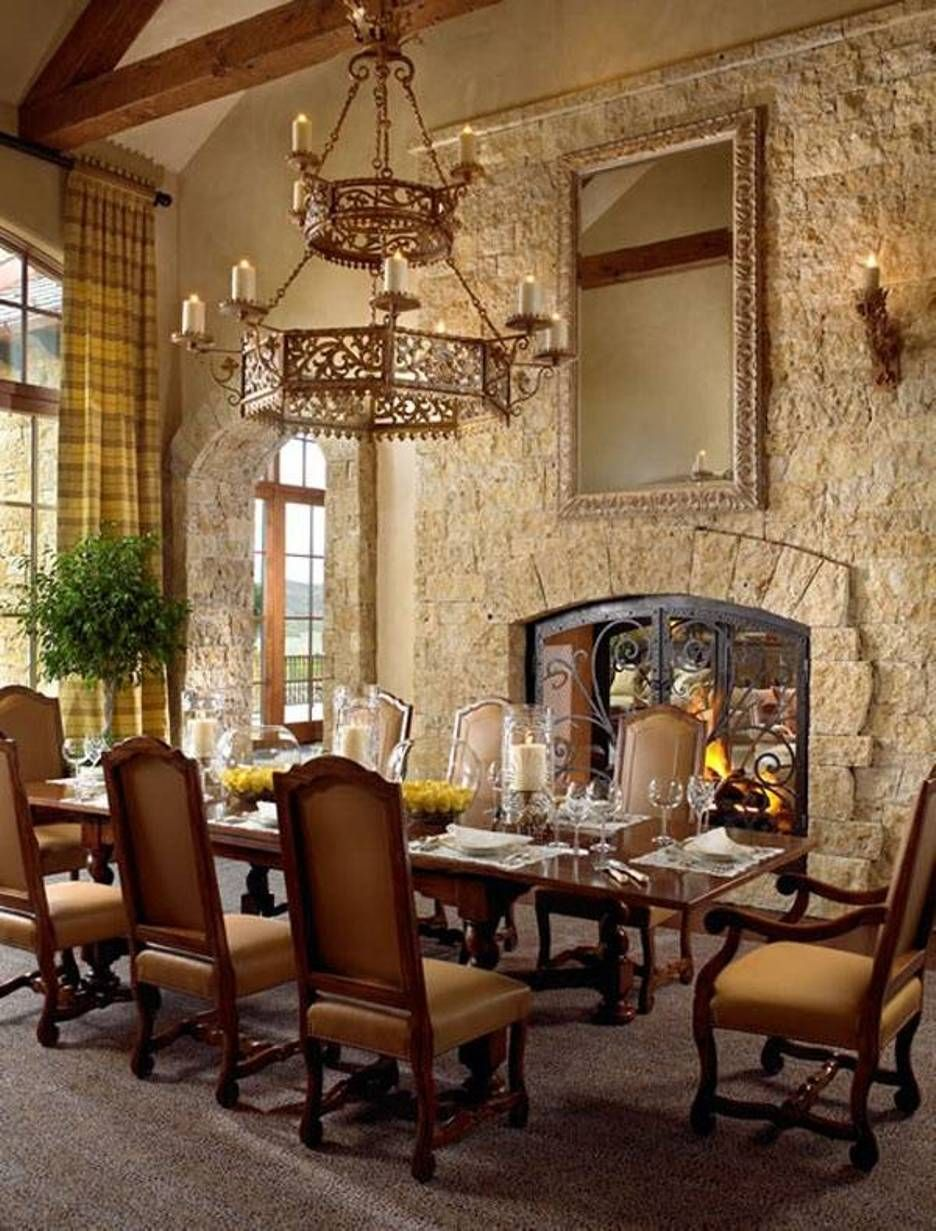 Tuscan Style Dining Room With Stacked Stone Fireplace And Sconces Chandelier Over Table Chairs