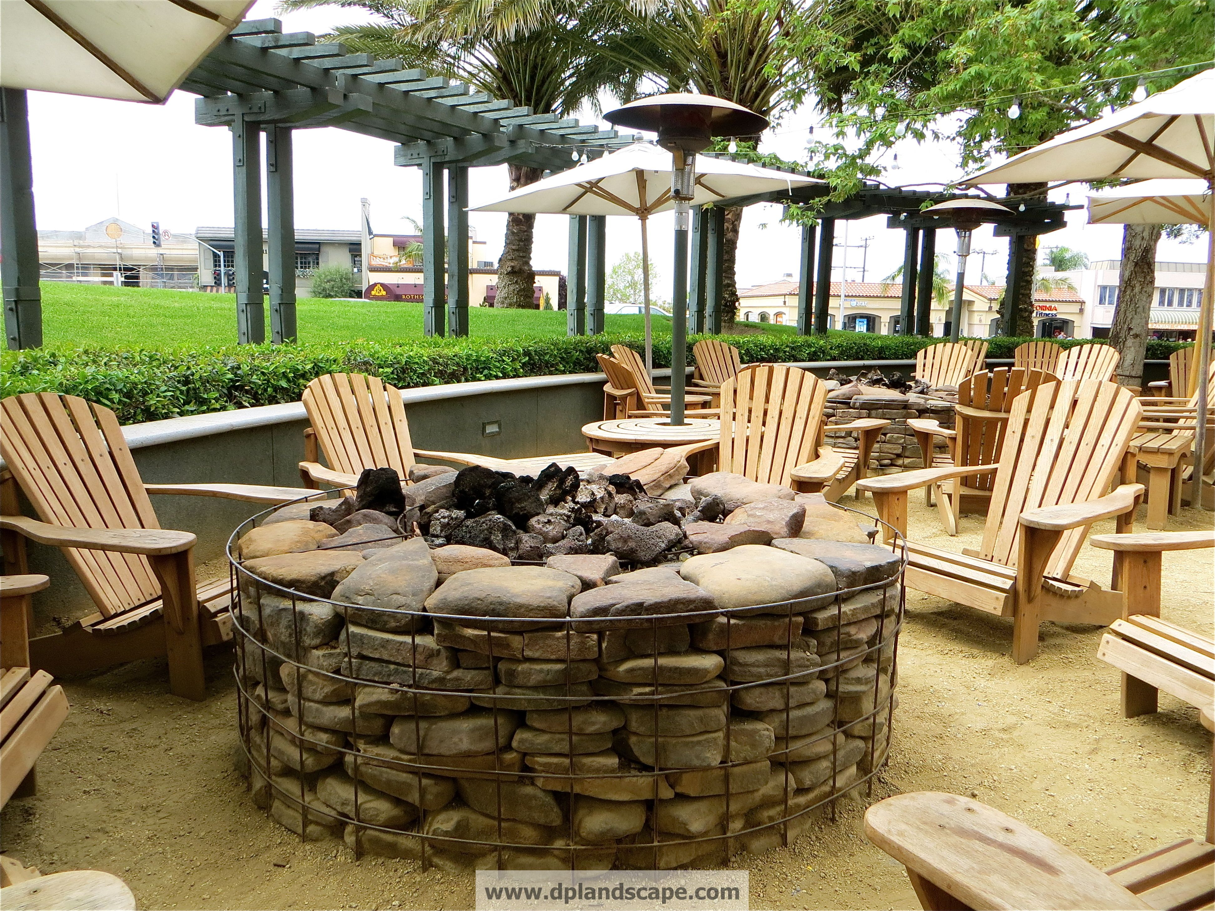 very cool gabion style stacked stone fire ring in the patio of the