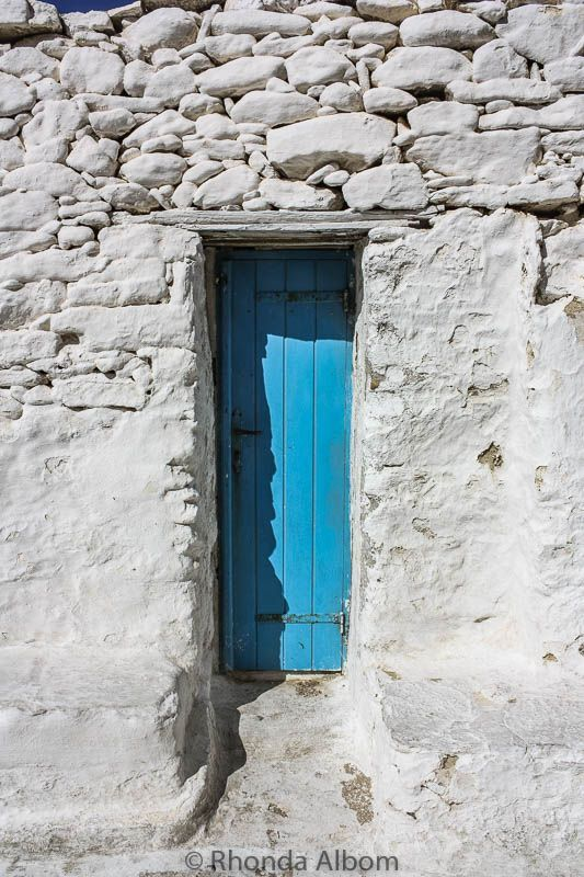 A tiny blue door in a home on Mykonos Greece. The island is a paradise of whitewashed buildings and beaches. #travel #europe #greece #mykonos #door