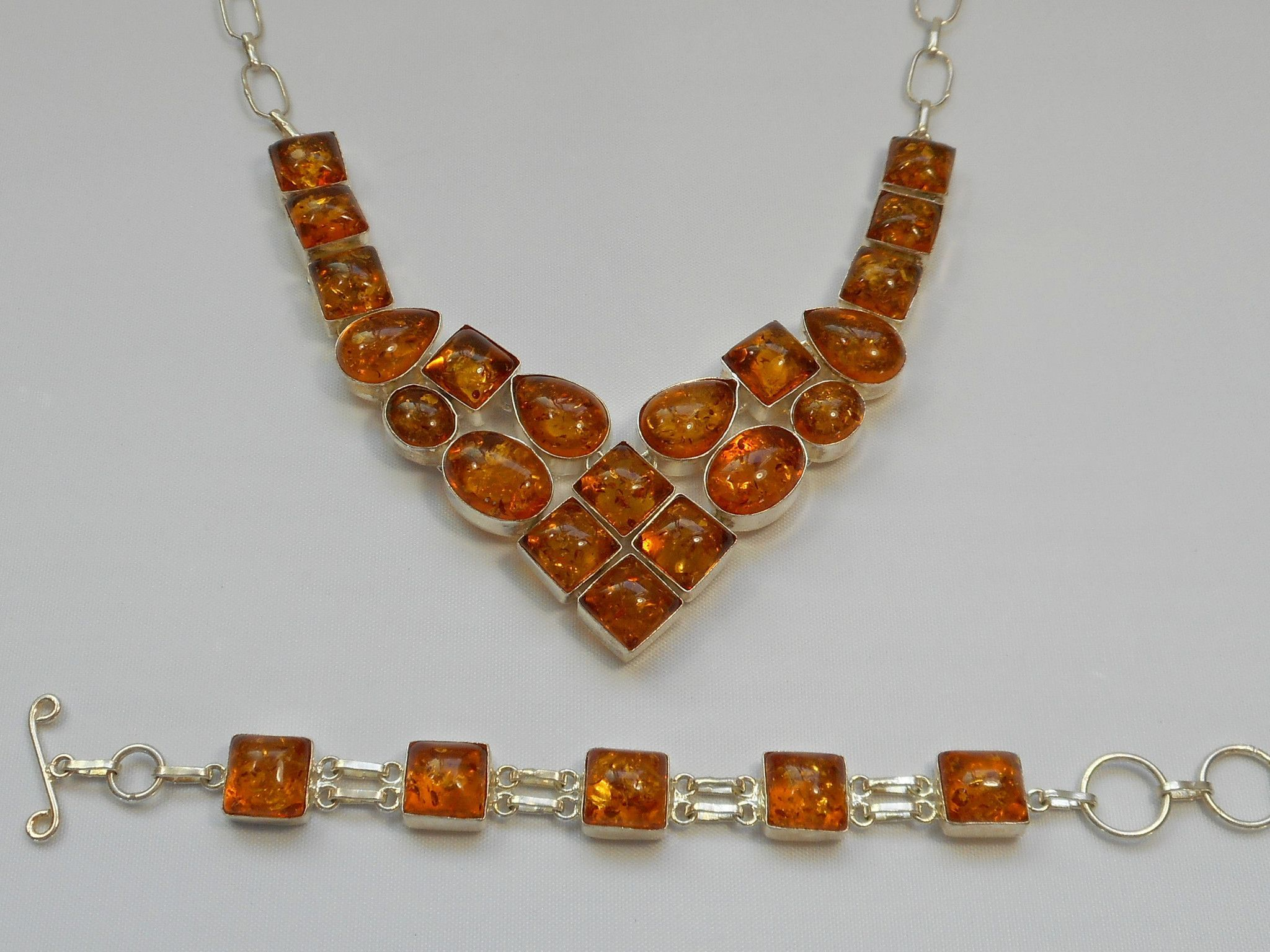 "*Amber Necklace 1: Twenty brilliant highly-polished translucent Amber gemstones rock this handmade necklace, set in 925-hallmarked sterling silver. Length: 15-20""  Widest center dimension: 1.75"""