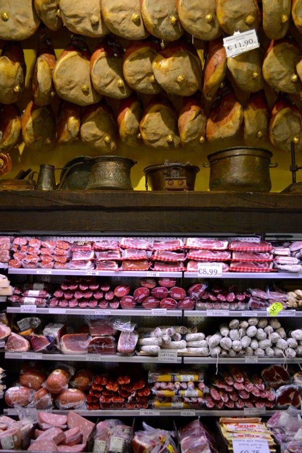 Prosciutto and other cured meats line shop walls in Bologna | Photo via www.ItalyProject365.com