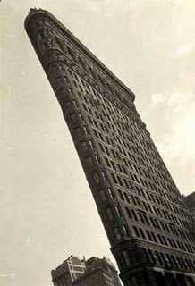 """El """"Flatiron"""", mítico edificio de Daniel Burnham en un Nueva York aun no vertical, rascacielos esquinero de acero y sueños, es visto por unos ojos que interpretan su verticalidad en términos de relación entre marco y figura.  La imagen se extiende y alarga, tensa las esquinas como una escalera y da idea de un edificio gracilmente inclinado. Como si el fotógrafo reclamara para la construcción la voluntad de ser aun más alto y afilado.  La imagen fue tomada por Walter Gropius en 1928. El mismo…"""