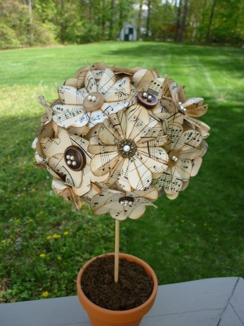 looks like paper flowers attached to a styrofoam ball stuck on a dowel and inserted into a clay pot