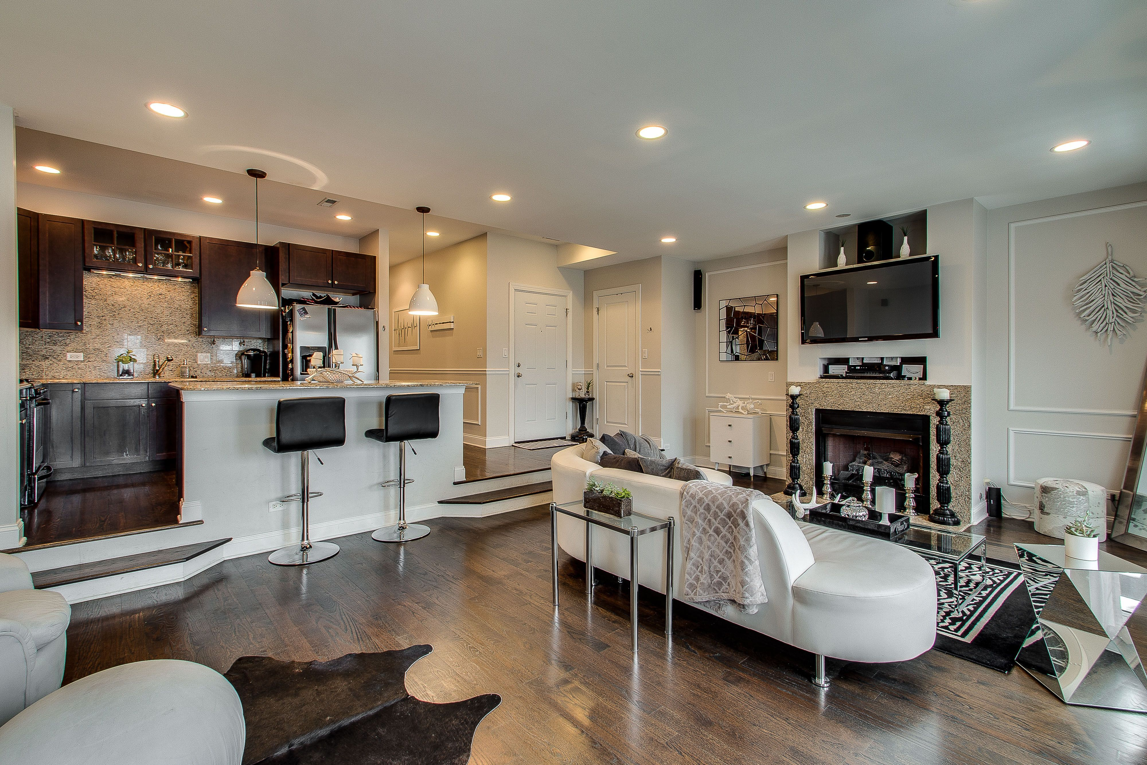 Modern open concept living room and kitchen with dark wood ...