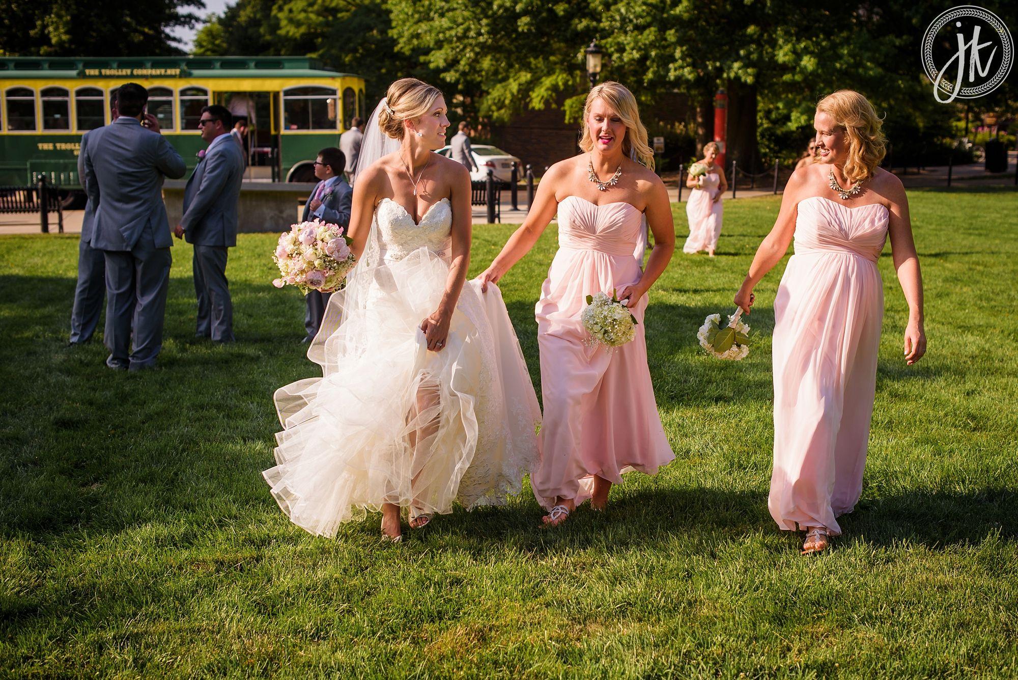 Bridesmaids help bride walk with her wedding dress across mizzou