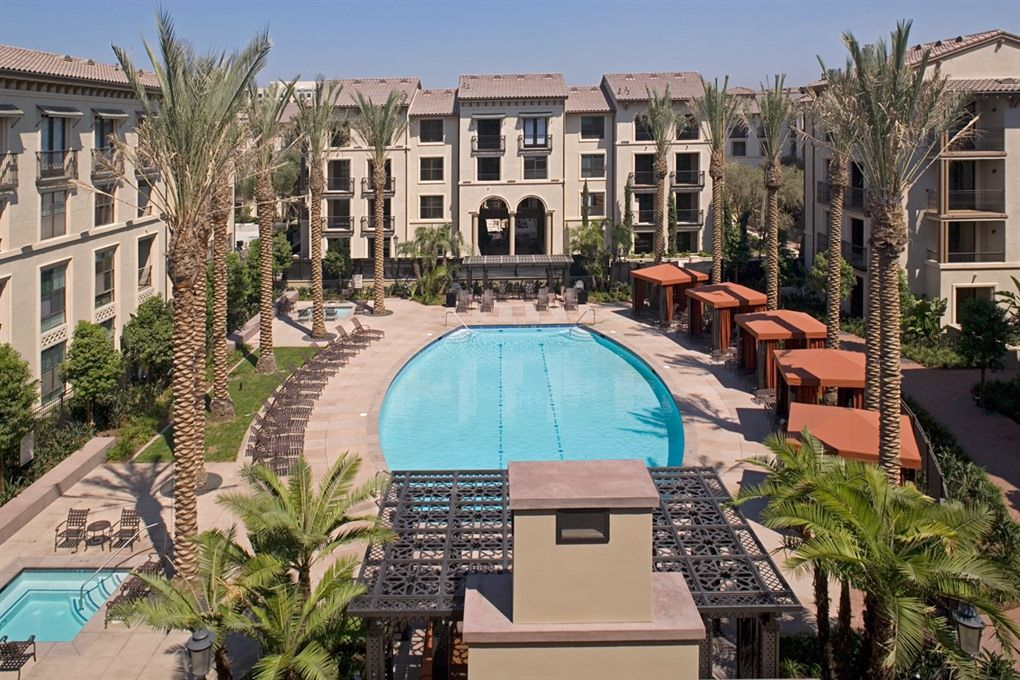 Refreshing Pool Surrounded By Cabanas And Lounge Chairs At The Village At Irvine Spectrum Center Apartments Apartment Resort Irvine Spectrum Pool