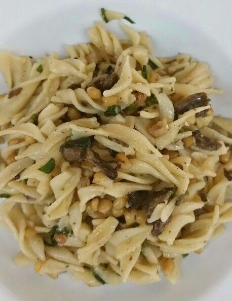 Comida vegetariana.  Pasta con perejil, hongos y granos de trigo. Sazonar con aceite de oliva y sal de ajo.