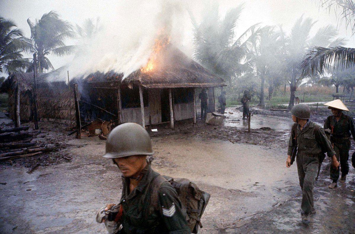 """In a hostile village Vietnamese infantrymen warily move past hut they set ablaze after they found it held Communist literature."""