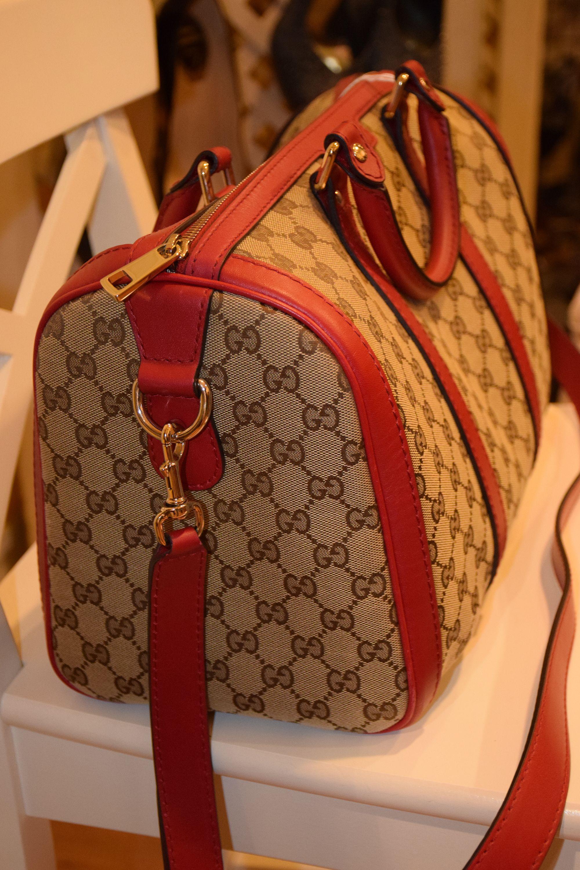 cd4b8aa39 Piezas metálicas doradas, bandolera regulable en rojo y asas de mano. Bolso  de la firma Gucci