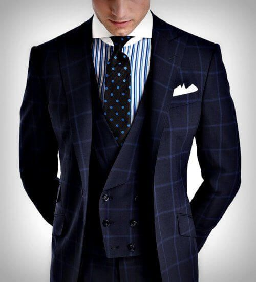 ネイビーのチェック柄のスリーピースのスーツに小紋柄のネクタイを合わせた