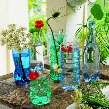 Plastc bottle vases reuse recycle . Des bouteilles en plastique découpées en forme de vase dans des couleurs bleu et vert.