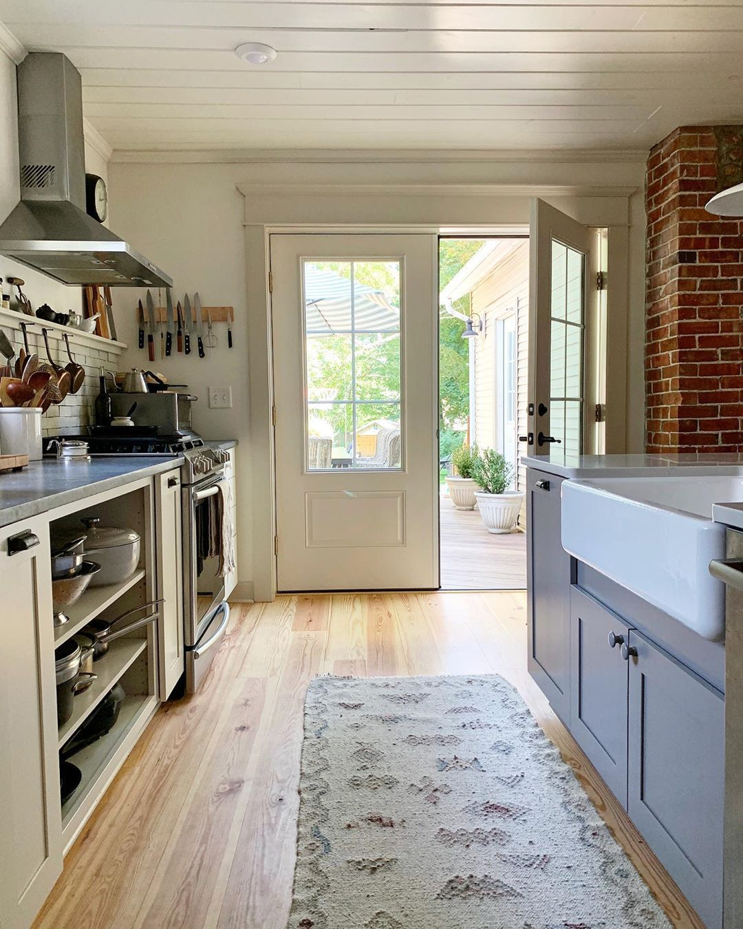 Open shelf next to stove with narrow cupboard for sheet ...
