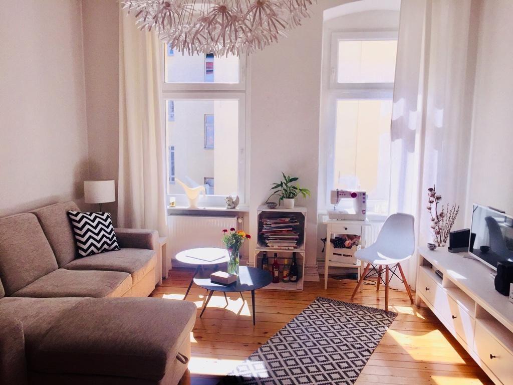 Helles Wohnzimmer mit schönem Dielenboden und gemütlichem Sofa