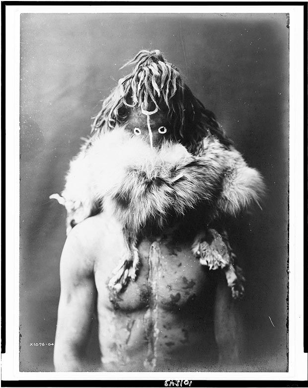 North America. Haschezhini – Navaho Indian, half-length portrait, facing front, wearing dark leather mask, fur ruff, nude torso painted with black and white splotches.