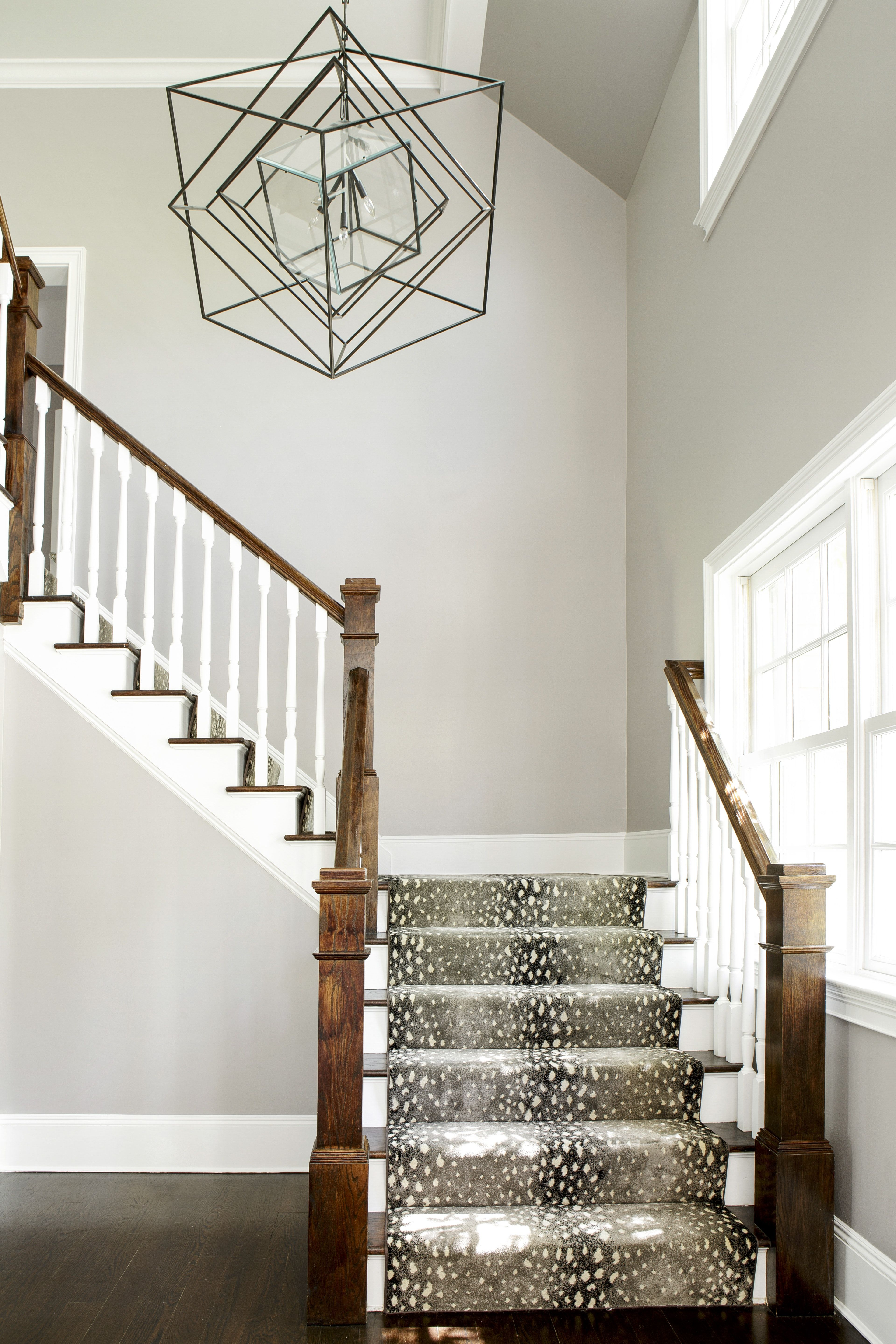 Bright foyer with animal print carpet on wrap around staircase statement light