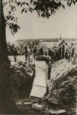 Nedtakingen av nazistøtta og anlegget på Stiklestad  Nedtakingen av Nazistøtta og anlegget på Stiklestad er under arbeid, 1945. Her er bautaen nedtatt, brukket og delvis nedgravd. Verdalinger står å ser på
