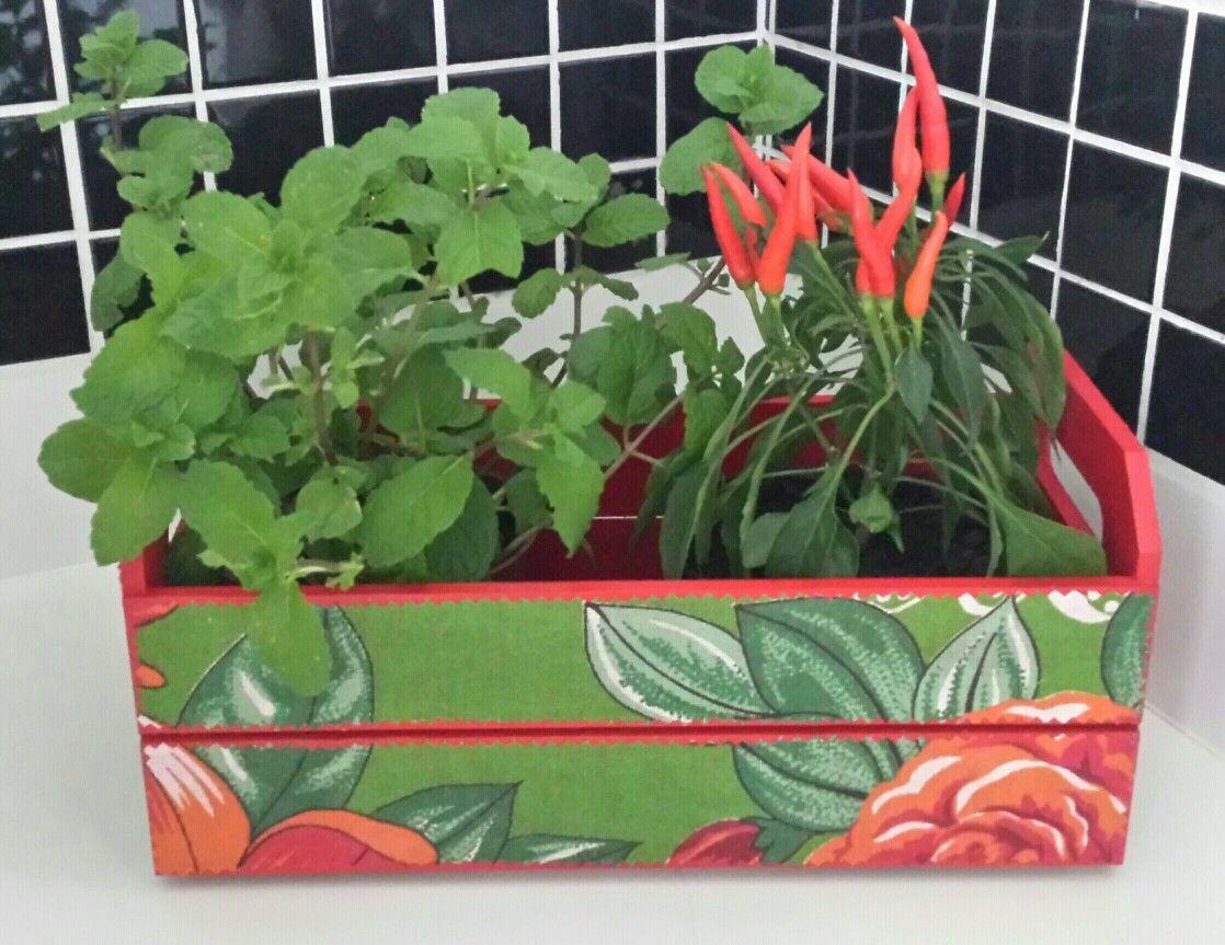 Em MDF, pintada, forrada com chita e envernizada. Acompanham dois vasinhos de ervas aromáticas.