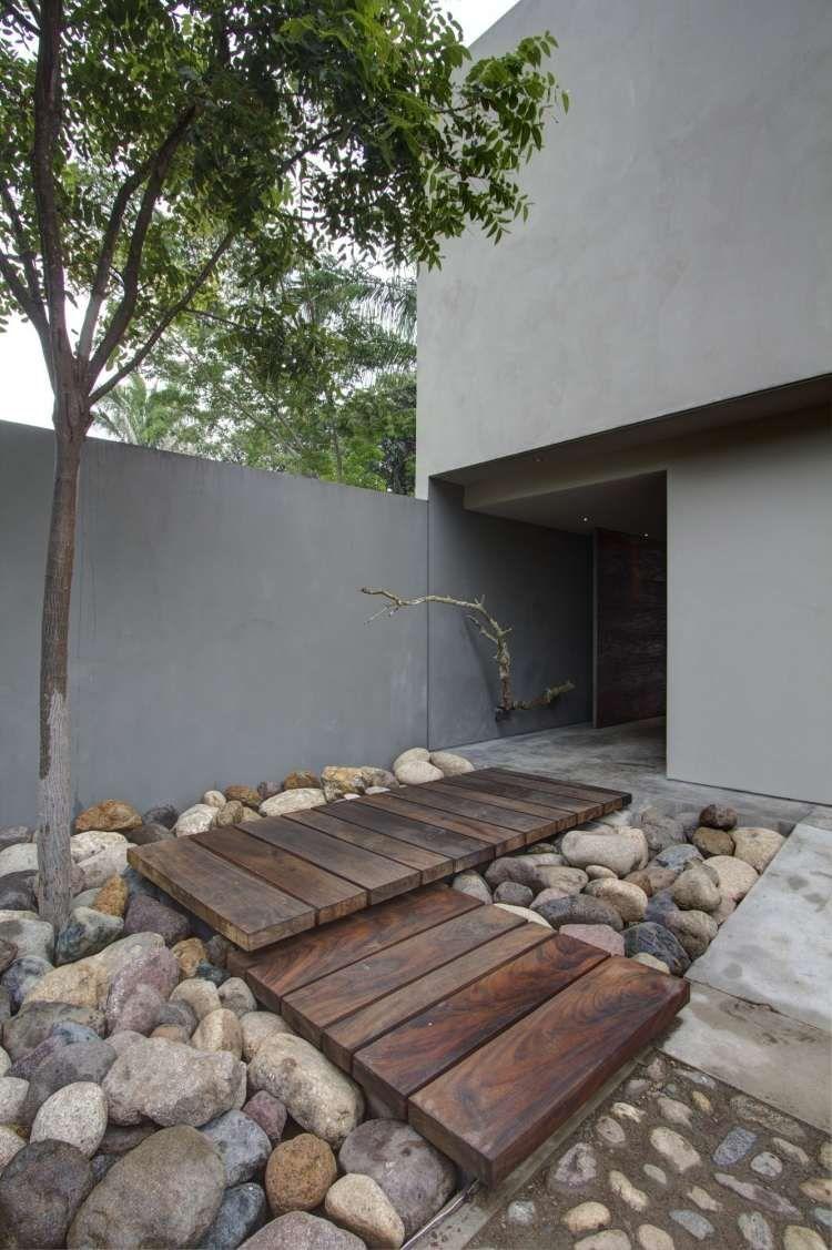 alle de jardin moderne en planches de bois massif et grosses pierres dans un esprit zen