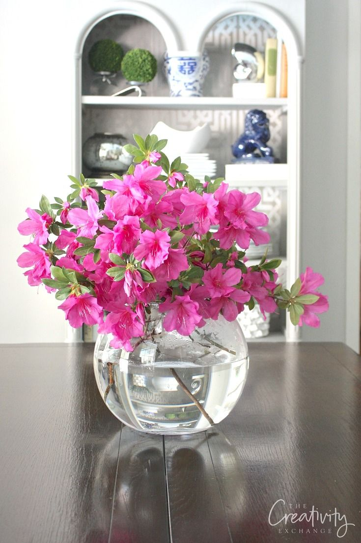 Large round glass globes are a great way to display flowers and branches from yard clippings
