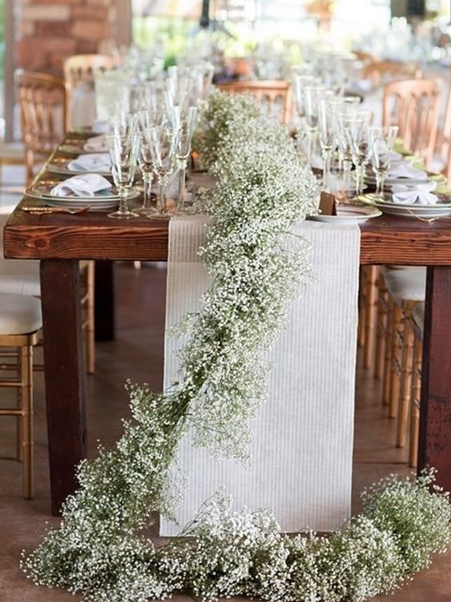 A runner of baby's breath going down the length of the table cascading off the ends with tall fluted votives with floating candles in lavender water, tall silver mercury glass votives, and low silver mercury glass votives
