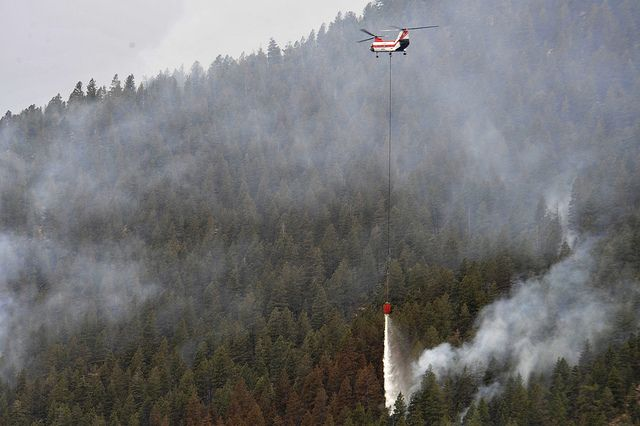 A helicopter dumps water on the Waldo Canyon Fire that spread to the outskirts of the Air Force Academy, Colo., June 28. The Waldo Canyon fire destroyed over 18,000 acres in the Colorado Springs area. (U.S. Air Force photo by Staff Sgt. Christopher Boitz)