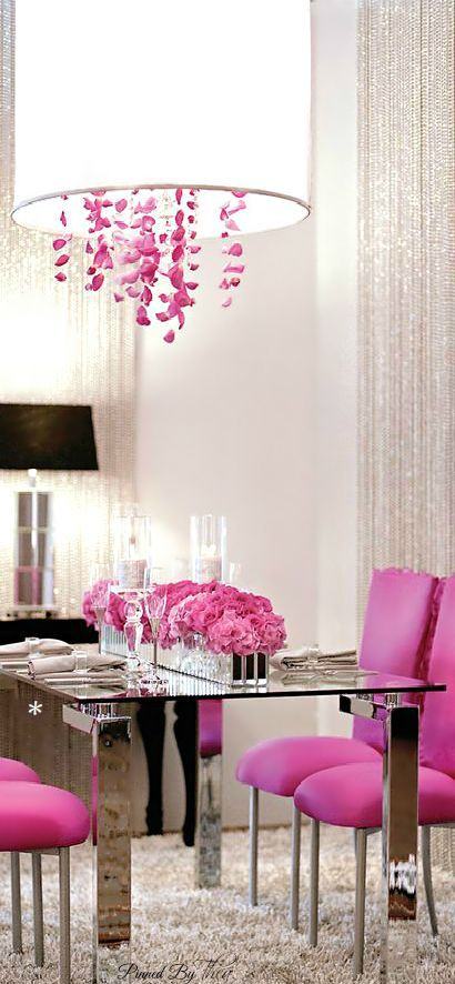 "Use a pop of color on a white palette, like these hot pink dining chairs and chrome table. Love the chandelier's pink ""crystals"" and the drum shade, which is bright yet soft lighting."