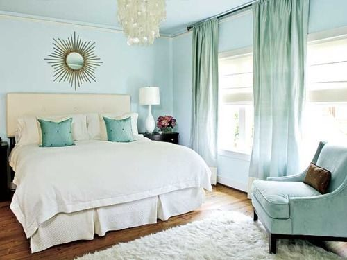 Bedroom with sky-blue walls and blue-green accents over white. There's that sun mirror again. And a capiz chandelier, all the greatest hits!