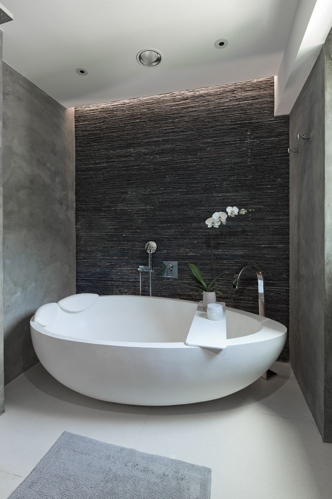 Photo of Egg-shaped bath in tight space with stone wall.