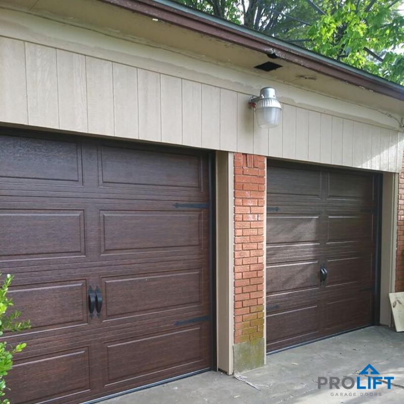 New Garage Doors Low Maintenance Steel Walnut Finish Decorative Hardware In 2020 Garage Doors Wooden Garage Doors Faux Wood Garage Door