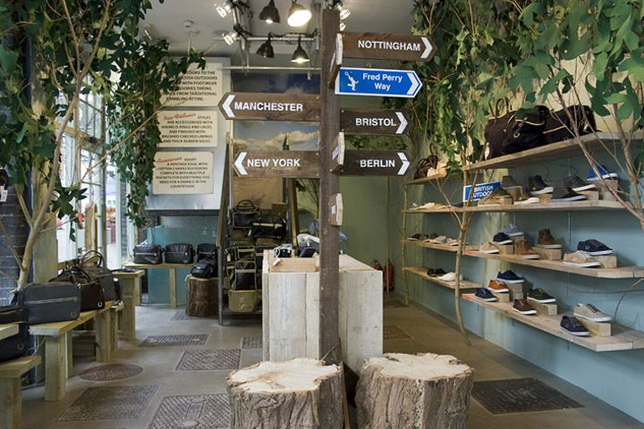 Fred Perry store by Studio XAG London. Great British Outdoors concept shop for accessories and footwear, with signposts, wooden stiles merchandising system, tree-trunk seating and trees bursting with felt foliage lining the walls to create a pocket of countryside in the city.