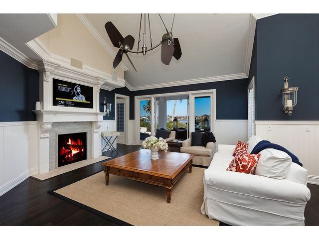 Dramatic dark blue and white family room with views of Naples Bay. Aqualane Shores in Naples, Fl