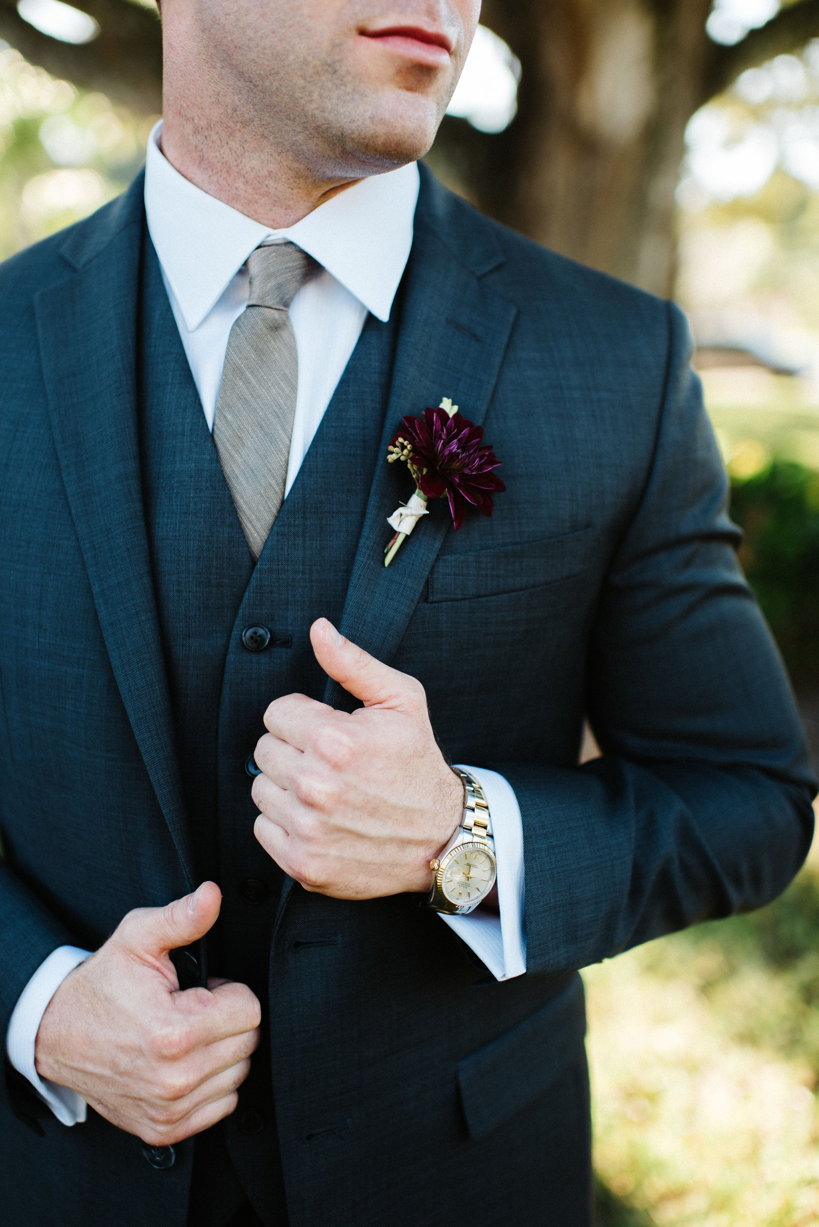 0730d8588579 the groom in a navy suit and grey tie wears a boutonniere of burgundy  ranunculus & greenery wrapped in cream satin ribbon.