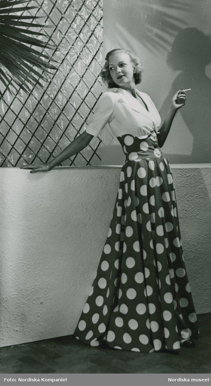 44908a4fd7fb Modell, fru Langlet, i hellång klänning med vit överdel och prickig kjol,  håller cigarett i handen. Foto: Erik Holmén för Nordiska Kompaniet