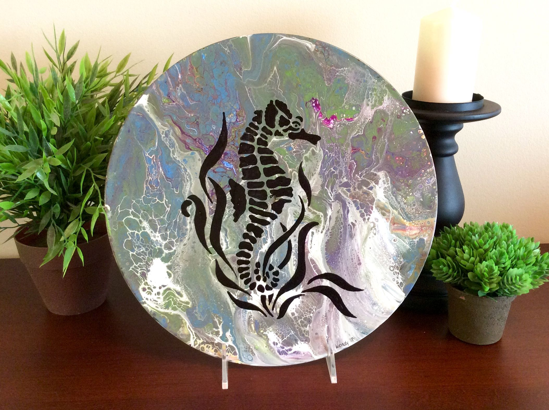 Fluid painting on vinyl record with seahorse silhouette.