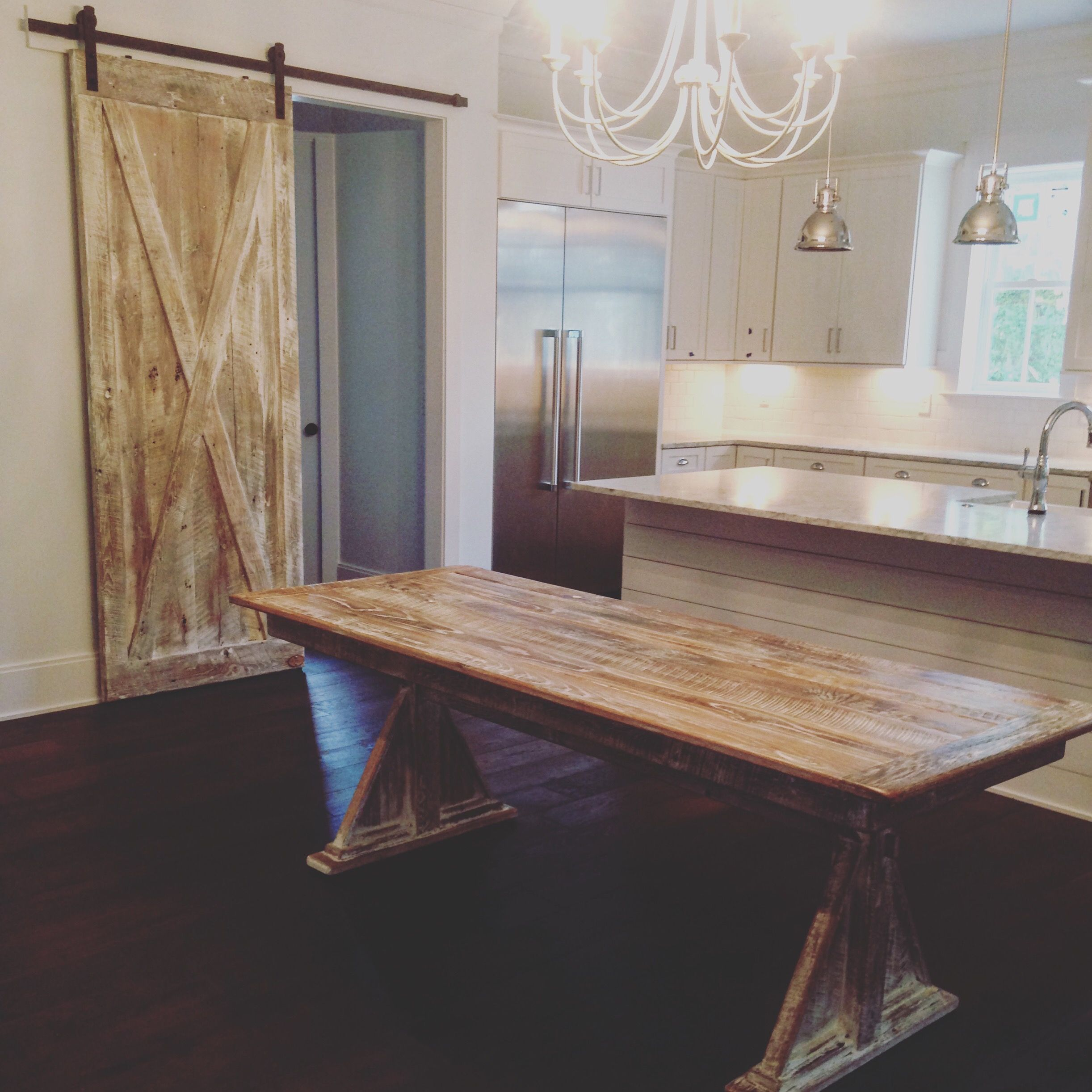 Reclaimed oak barn wood trestle table and sliding barn door with white lime wash