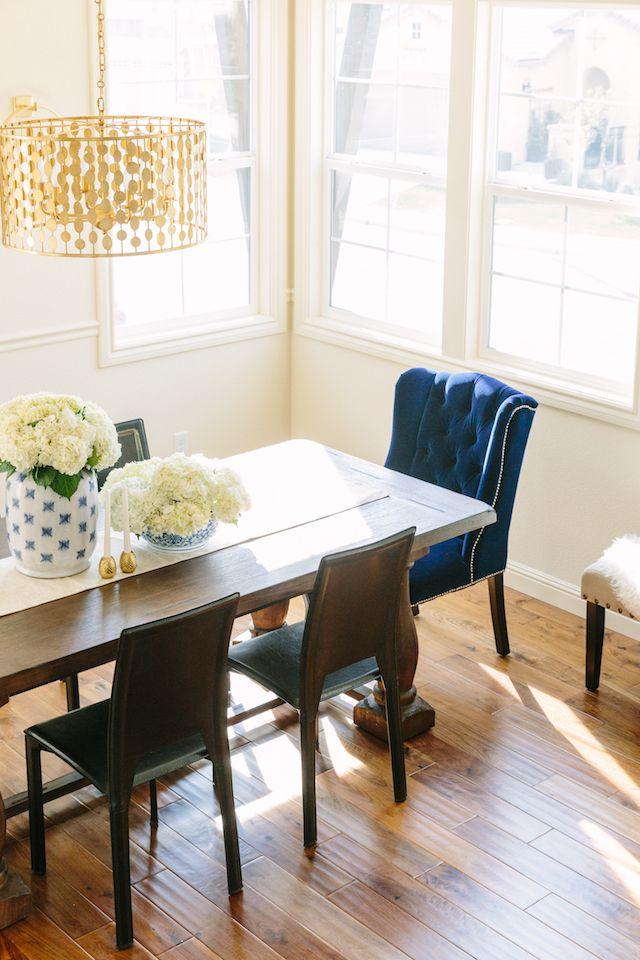 Eggshell Home Rosanna Bassford Modern Glam Dining Room Gold Chandelier Blue Velvet Chair Wood Table Walnut