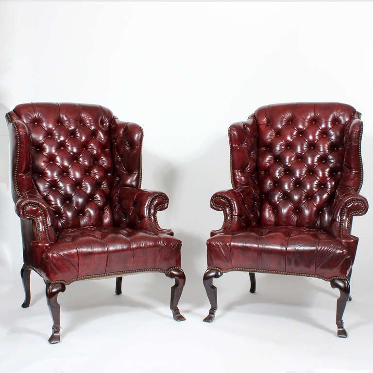 A pair of red leather tufted high back wing chairs with