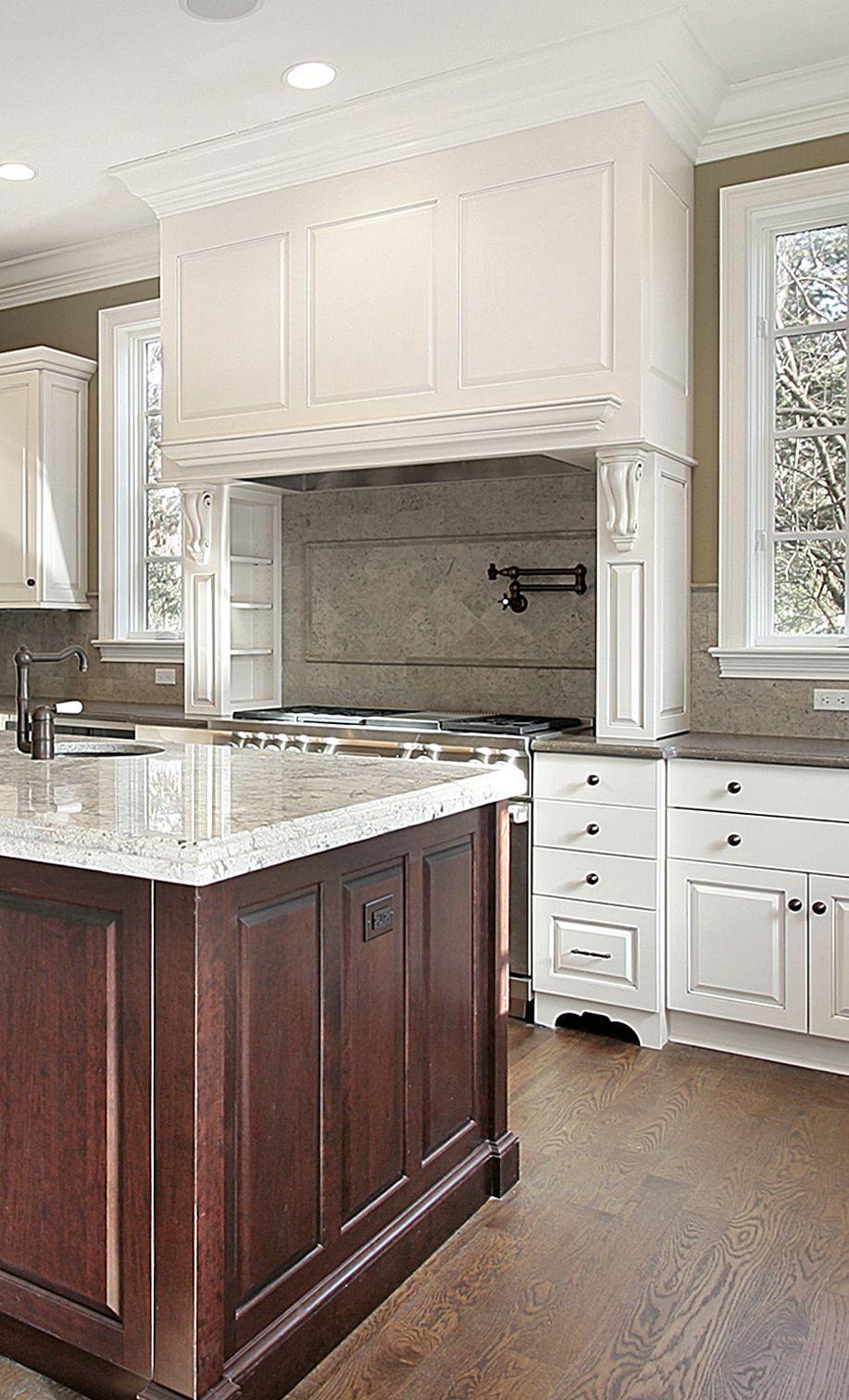 Cream kitchen with large decorative range hood and cherry