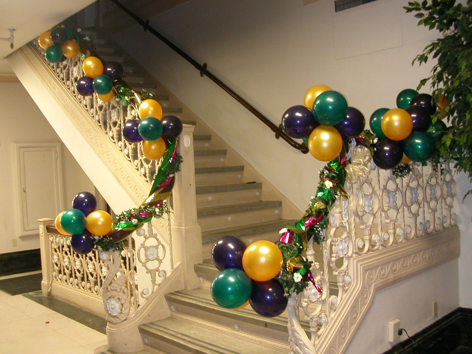 Dress up boring stair rails with colorful balloon clusters for Balloon cluster decoration