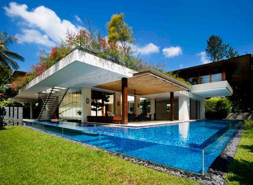 If ever there was a house to make my jaw drop, this might just be it. Located in Singapore, the Tannga House is a tropical paradise with the home being built around a green courtyard to enjoy the hot climate. Designed by Guz Architects, the L-shaped house is all about the outdoors and the lush landscape that surrounds it. But that's not all – the house also features an L-shaped, glass-walled pool that can be viewed through a window from a lower floor in the home. I'm sold.