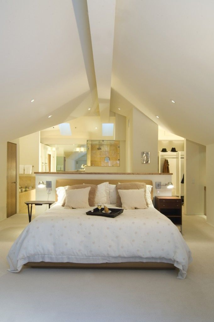 An Open Concept Attic Space Houses A Bedroom Closet And Bathroom The Bed Is Situated Against A Half W Loft Conversion Bedroom Attic Master Bedroom Loft Room