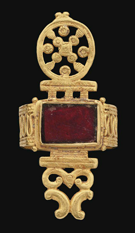 A LATE ROMAN GOLD AND GARNET RING   CIRCA 4TH CENTURY A.D.   The openwork hoop with band of continuous loops with plaited bands either side, the rectangular bezel with garnet inlay, the bezel projections with a pierced-work roundel on one side and peltae on the other
