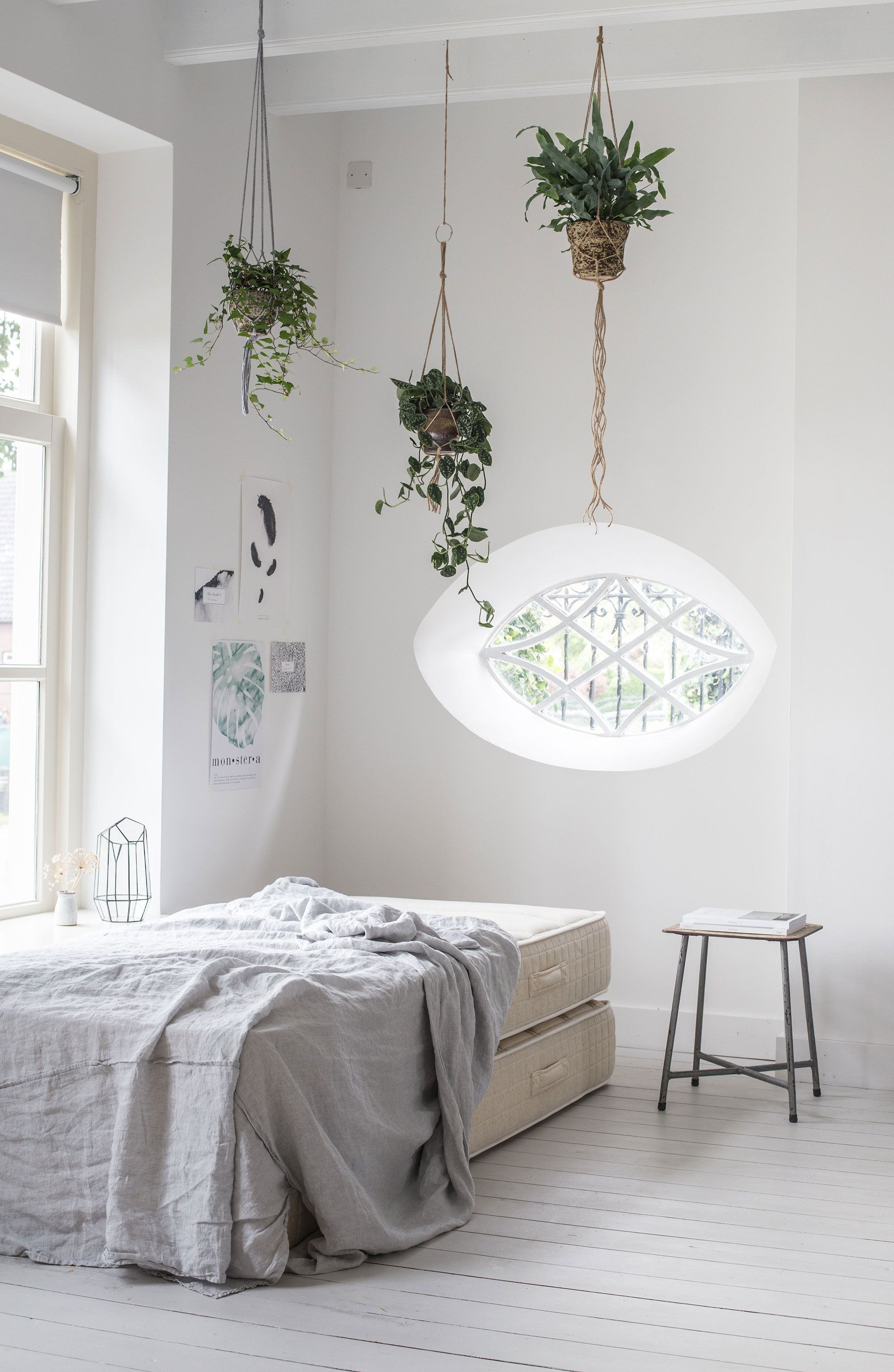 sustainable mattress in white loft house with white wooden floor and hanging plants. Special oval window and gray linen sheets from By Molle.
