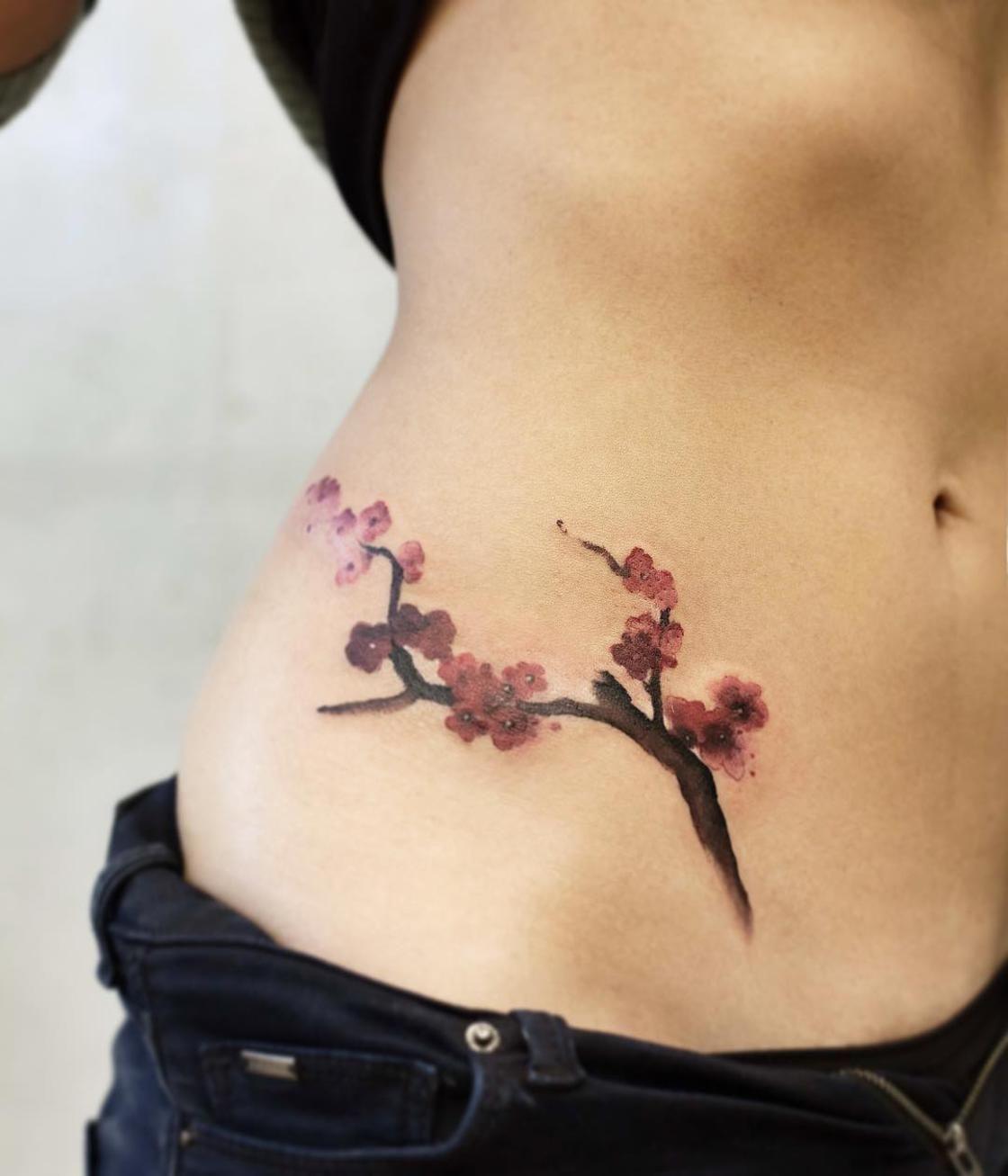 Impresionantes tatuajes de flores en el abdomen de una mujer
