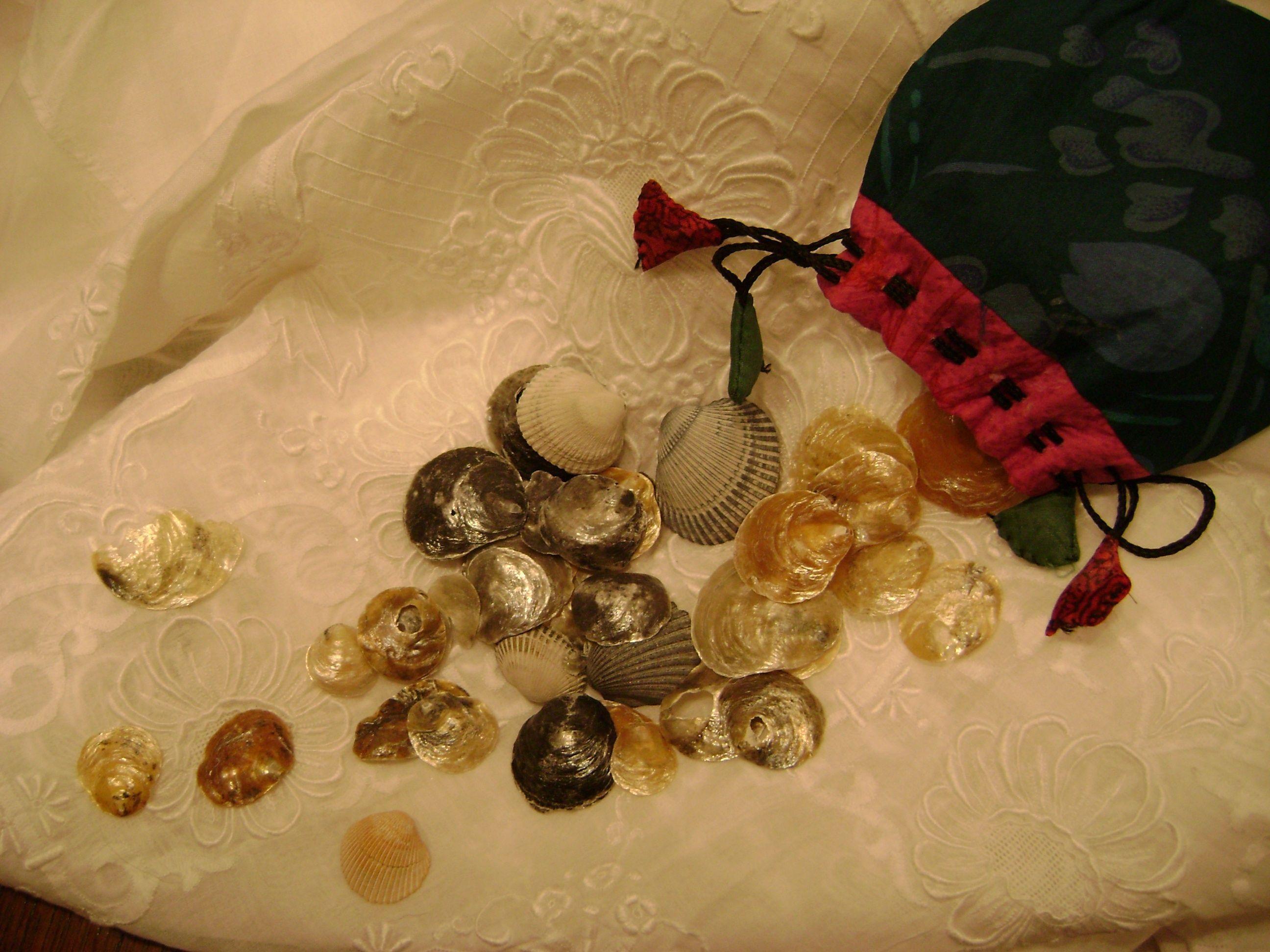 Drawstring purse spilling seashells onto  embroidered white linen.