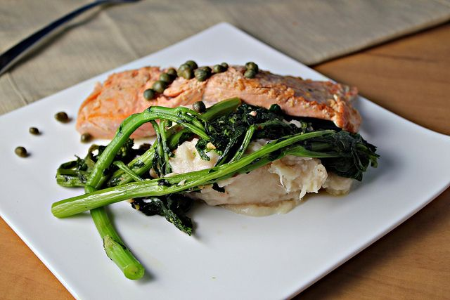 salmon in a lemon-caper sauce over mashed cannellini beans and broccoli rabe