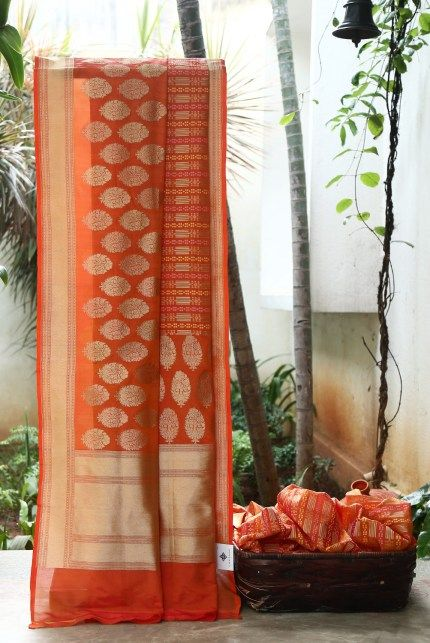 THE LUSTROUS ORANGE IRIDESCENT PINK BENARES TUSSAR SILK HAS ZARI BHUTTAS ALL OVER. THE GOLD ZARI BORDER INTRICATELY WOVEN WITH HINT OF PINK WHICH FLOWS INTO THE PALLU GIVES IT DIVINE LOOK.