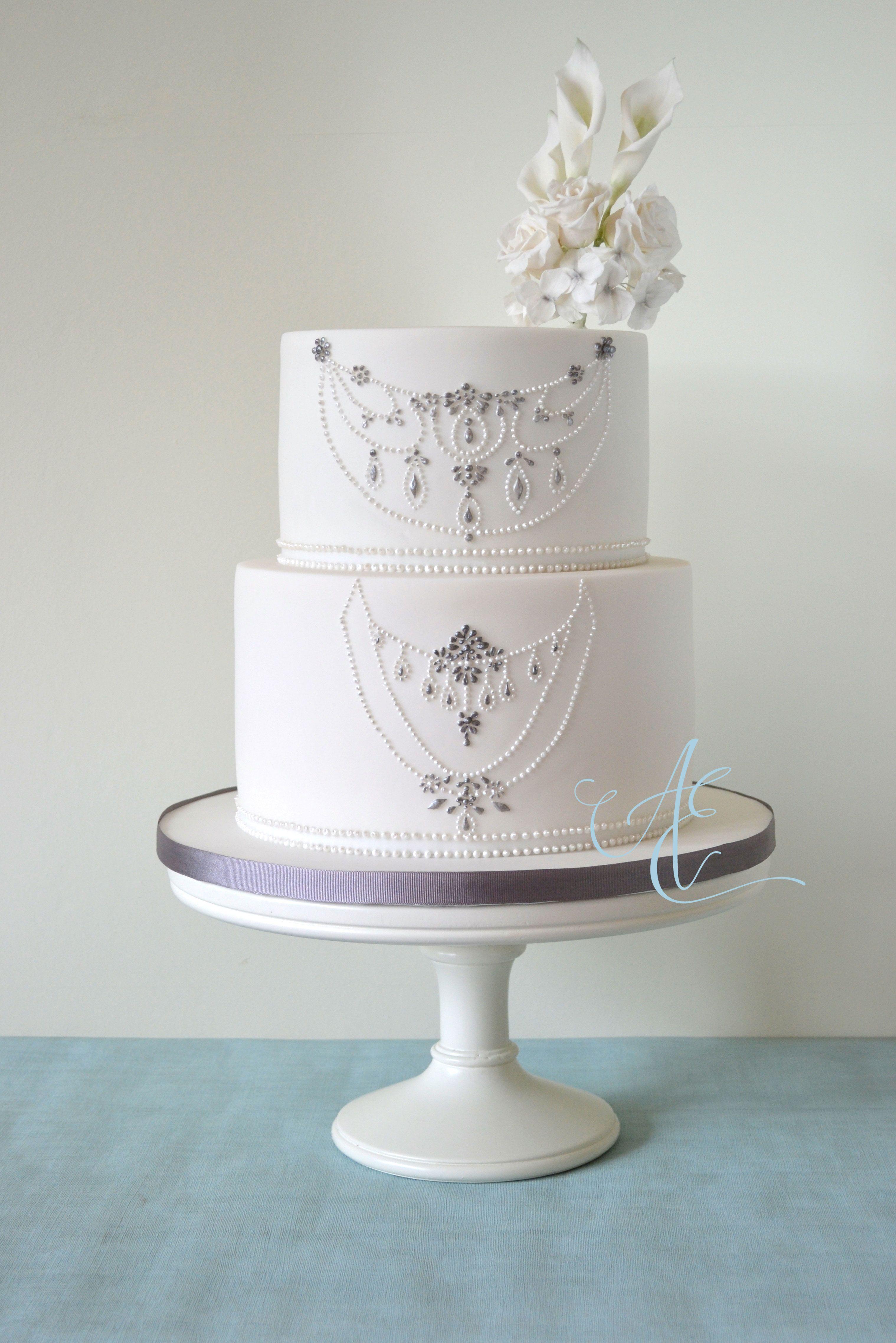 Elegant white u silver wedding cake with hand piped design taken